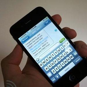 fotografia di uno smartphone con una mano che sta componendo un SMS